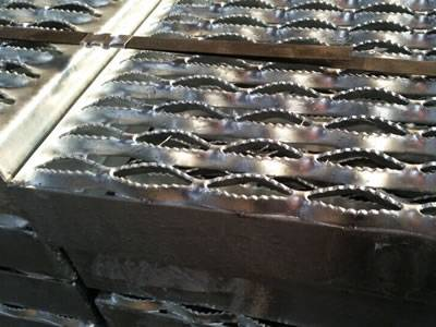 Several bundles of diamond safety grating on the ground.