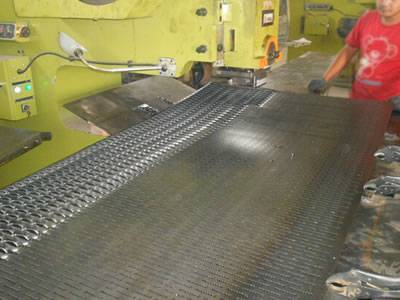 A worker is operating the machine to produce the diamond safety grating.