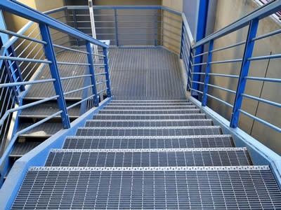 It is a blue stair tread make by steel grating and there is handrail.