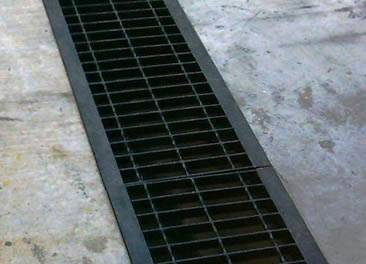 A painted carbon steel grating is covering a trench.