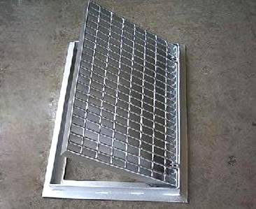 A hinged drainage trench box grate with serrated surface.