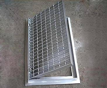 A drainage trench box grate with hinges and smooth surface.