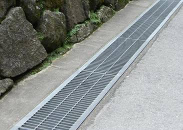 The side angled drainage trench grates are installed on the ground.