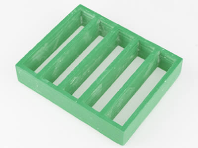 A Piece Of Green Color FRP Molded Grating With Rectangular Opening On The  Gray Background.