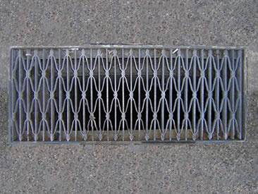 An aluminum riveted grating is covering a trench on the ground.