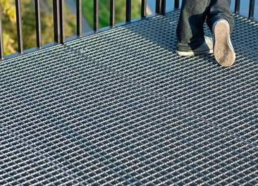 The serrated steel grating is installed on the balcony and a man is standing on it.