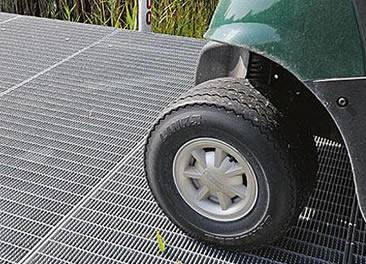 A car is driving on the serrated steel grating.