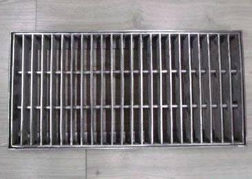 A swage-locked drainage trench box grate is installed on the wood floor.