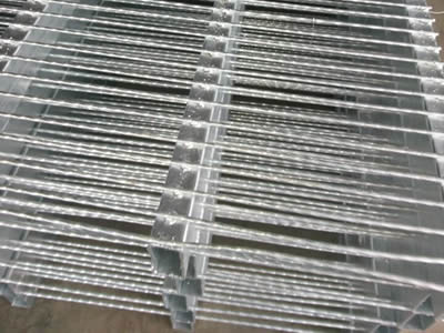 Several pieces of hot dipped steel bar grating on the ground.