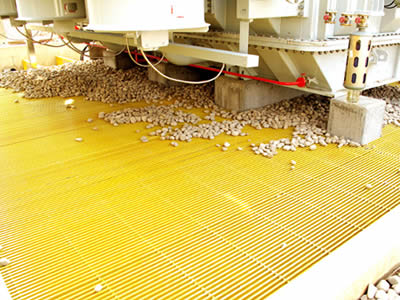 Yellow color transformer gratings are lay on the transformer bay and several stones on them.