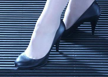 A woman wearing high-heeled shoes is standing on the close mesh walkway grating.